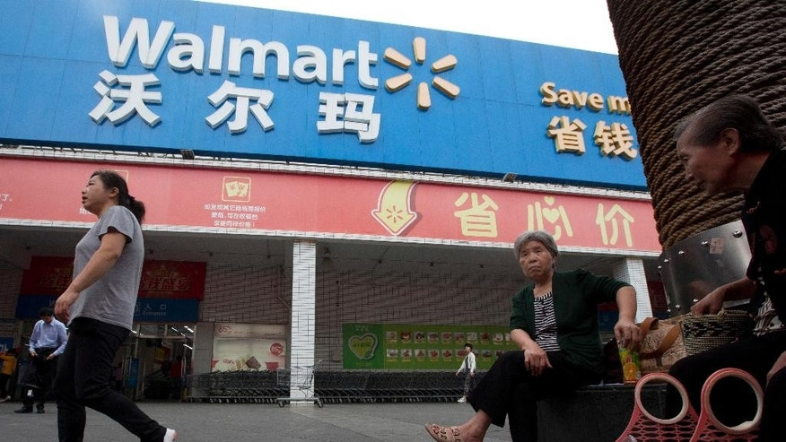 In this Wednesday, Nov. 11, 2015, photo, residents past by a Wal-Mart in Shenzhen, in southern China's Guangdong province. Wal-Mart faces protests by employees in China over what they say is a drastic change in work schedules under a system rolled out in June 2016 as the company overhauls its struggling business amid slowing economic growth and competition from e-commerce. (AP Photo/Ng Han Guan)