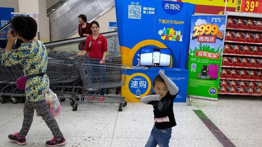 In this Wednesday, Nov. 11, 2015, photo, a child walks past an employee at a Wal-Mart in Shenzhen, in southern China's Guangdong province. Wal-Mart faces protests by employees in China over what they say is a drastic change in work schedules under a system rolled out in June 2016 as the company overhauls its struggling business amid slowing economic growth and competition from e-commerce. (AP Photo/Ng Han Guan)