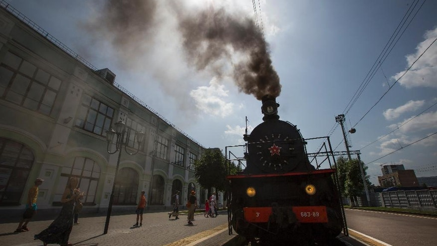 In this photo taken on Saturday, June 18, 2016, a steam locomotive is preparing to depart from a station in Moscow, Russia. Moscow's railway museum, which has a collection of 60 engines, cars and other equipment preserved in full working condition, runs steam-hauled tours across the Russian capital. (AP Photo/Alexander Zemlianichenko)