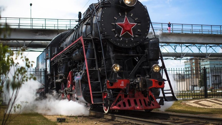 In this photo taken on Wednesday, July 6, 2016, a steam locomotive moves a locomotive depot in Moscow, Russia. Moscow's railway museum, which has a collection of 60 engines, cars and other equipment preserved in full working condition, runs steam-hauled tours across the Russian capital. (AP Photo/Alexander Zemlianichenko)
