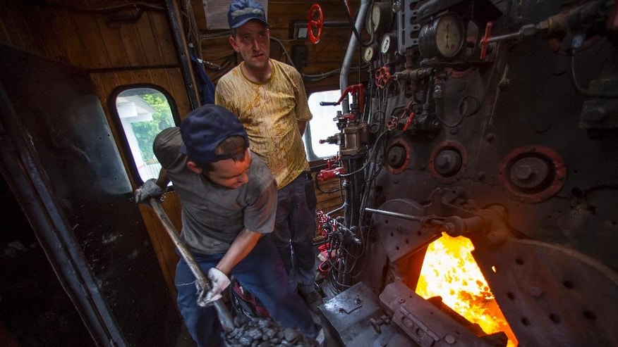 In this photo taken on Saturday, June 18, 2016, an assistant engine driver throws coal into a locomotive's fire chamber in Moscow, Russia. Moscow's railway museum, which has a collection of 60 engines, cars and other equipment preserved in full working condition, runs steam-hauled tours across the Russian capital. (AP Photo/Alexander Zemlianichenko)