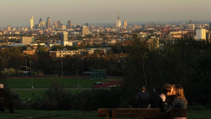 FILE - in this file photograph dated Friday April 8, 2011, a couple kiss on Parliament Hill at sunset on Hampstead Heath in London, overlooking a view of parts of London including St Paul's Cathedral, horizon centre right, dwarfed by the then new Shard skyscraper, behind, at that time still under construction. Henry Pryor, who has helped people buy homes in London for more than 30 years, says only war would be a bigger threat to the housing market than the conditions it faces now after Britain's vote to leave the European Union. (AP Photo/Matt Dunham)