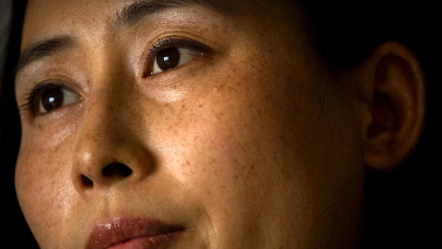 In this Wednesday, July 6, 2016 photo, Yuan Shanshan, the wife of detained Chinese lawyer Xie Yanyi, pauses during an interview in their apartment in Miyun, on the outskirts of Beijing. The Chinese government launched its largest-ever crackdown against human rights lawyers and activists on July 9, 2015, capturing or questioning of hundreds of people nationwide in a campaign that sent a chill over the country's legal system. Nearly two dozen lawyers, including Xie, remain under detention and face charges including subverting state power - charges condemned by international human rights groups and Western governments - while in the outside world, their families struggle with the fallout. (AP Photo/Mark Schiefelbein)