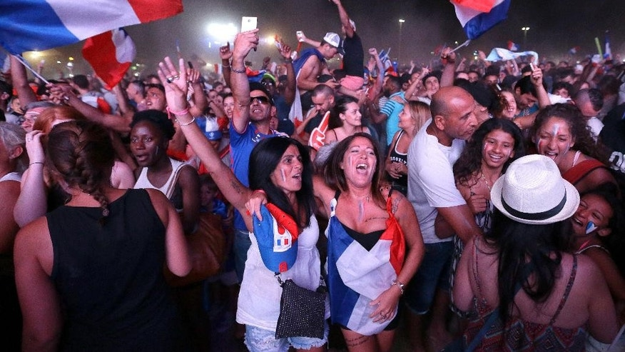 French supporters celebrate France's victory in the Marseille fan zone after the Euro 2016 semifinal soccer match between Germany and France,Thursday, July 7, 2016 in Marseille, southern France. France won 2-0. (AP Photo/Claude Paris)