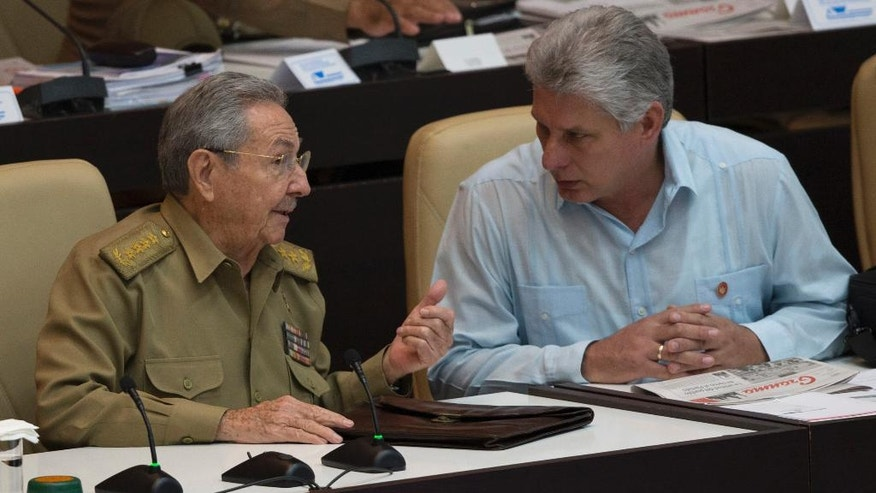 Cuba's President Raul Castro, left, talks with Vice President Miguel Diaz Canel during the opening of the National Assembly session in Havana, Cuba, Friday, July 8, 2016. Cuba's parliament has convened for one of its one of its twice-annual plenary sessions amid warnings from government officials that the country faces energy restrictions during tough fiscal times.  (Ismael Francisco, Cubadebate via AP)