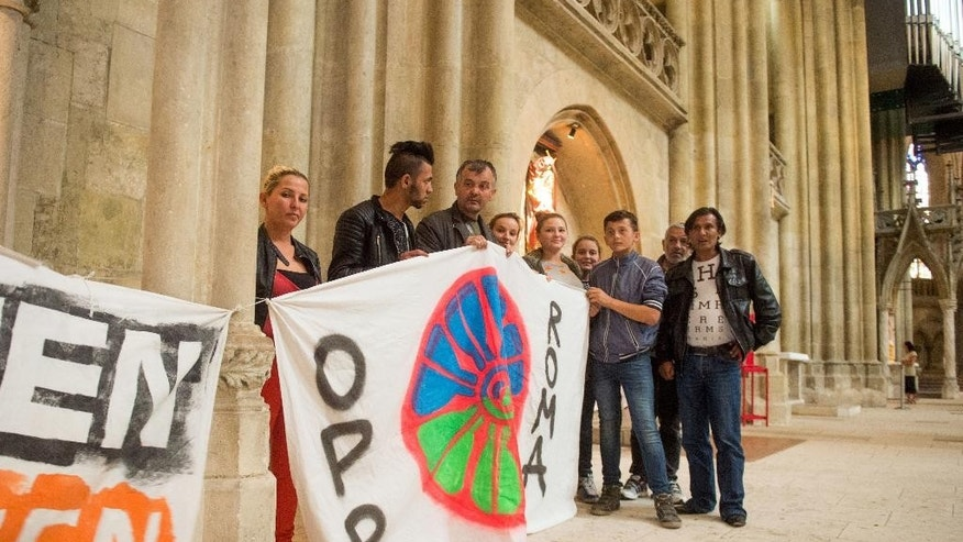 In this photo taken Wednesday, July 6, 2016, refugees hold up banners at the St. Peter's Cathedral in Regensburg, southern Germany. A group of 45 ethnic Albanians from Kosovo have been camped out in Regensburg Cathedral since Tuesday in protest against their deportation. The archdiocese in Regensburg said it is negotiating with the group to move to a different building where they will have access to washing facilities and a kitchen. (Armin Weigel/dpa via AP)