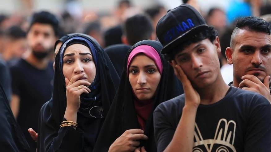 People wait for family members who went missing as paramedics look for burned bodies inside a mall at the scene of Sunday's massive truck bomb attack claimed by the Islamic State group in the Karada neighborhood, Baghdad, Iraq, Thursday, July 7, 2016. (AP Photo/Khalid Mohammed)