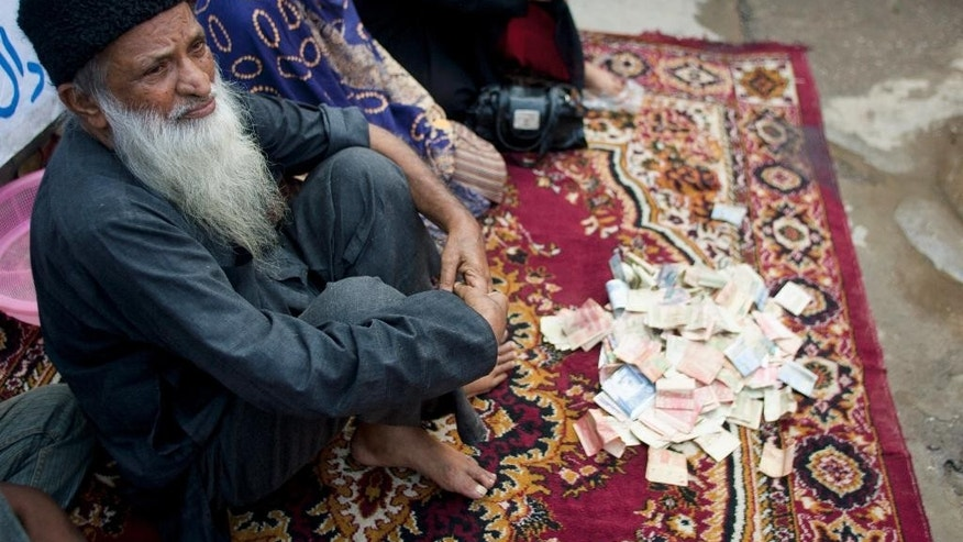 FILE - In this Monday, Aug. 2, 2010 file photo, Pakistan's humanitarian leader Abdul Sattar Edhi collects donations at a roadside in Peshawar, Pakistan. The family of Pakistan's legendary philanthropist Abdul Sattar Edhi say he has died at a hospital in Karachi. (AP Photo/Anjum Naveed, File)
