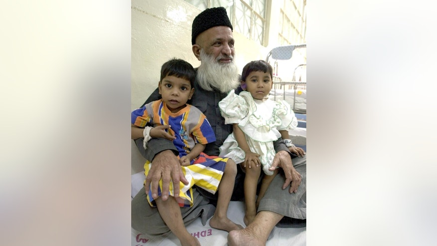 FILE - In this March 16, 2002 file photo, Pakistan's renowned social worker Abdul Sattar Edhi holds infants at Edhi Childcare Center in Karachi, Pakistan. The family of Pakistan's legendary philanthropist Abdul Sattar Edhi say he has died at a hospital in Karachi. (AP Photo)