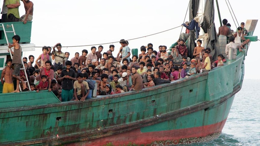 FILE - In this May 20, 2015, file photo, migrants including Myanmar's Rohingya Muslims sit on their boat as they wait to be rescued by Aceh fishermen on the sea off East Aceh, Indonesia. For nearly 30 years, Aung San Suu Kyi starred as arguably the world's most prominent and revered political prisoner, a courageous champion of human rights and democracy in her military-ruled nation. As she completes her first 100 days in power, the Nobel Prize laureate's halo has all but vaporized on the global stage: Suu Kyi is being assailed for ignoring the plight of the oppressed Rohingya Muslims, failing to stop atrocities against other ethnic minorities and abetting moves to erase from collective memory the bloody history of the generals she replaced.  (AP Photo/S. Yulinnas, File)