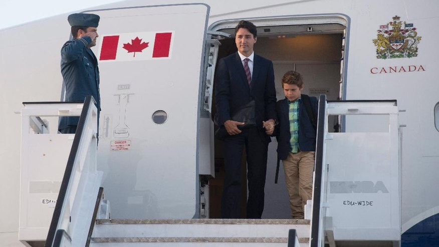 Canadian Prime Minister Justin Trudeau and his son, Xavier, disembark a government plane as they arrive in Warsaw, Poland, Friday July 8, 2016. (Adrian Wyld/The Canadian Press via AP)