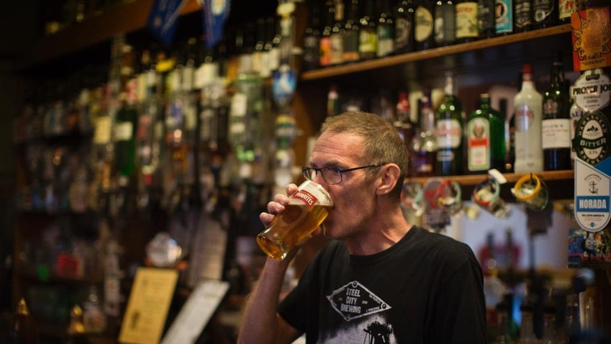 In this Tuesday, July 5, 2016 photo, Bram, 58, drinks a beer at his pub Hand and Heart, at Millfield neighborhood in downtown Peterborough, East of England. Bram said he knows some of the migrants are good, hard-working people. Still, he doesn't think they're trying hard enough to integrate. (AP Photo/Emilio Morenatti)