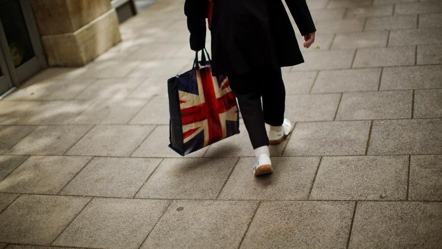 In this Tuesday, July 5, 2016 photo, a woman carrying a bag decorated with a Great Britain's union flag, walks a long a street in downtown Peterborough, East of England. Many people who voted for Britain to get out of the European Union look at multi-ethnic Peterborough as a warning example. They say British identity has been eroded in parts of the city where migrants have moved in and pubs have been replaced by shawarma shops or ethnic food stores. (AP Photo/Emilio Morenatti)