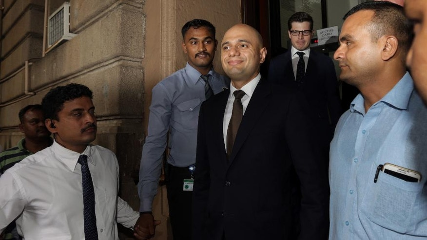 Britain's Business Secretary Sajid Javid, center, leaves after a meeting with Tata Steel executives amid reports that the Indian conglomerate is prepared to sell some of its U.K. plants, in Mumbai, India, Friday, July 8, 2016. Tata is looking to dispose of its specialty steel businesses in Hartlepool, Rotherham and Stocksbridge, but has so far held off any decision on what to do with its plant in Port Talbot, in Wales. (AP Photo/ Rajanish Kakade )