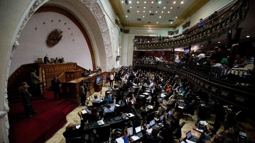 In this Jan. 14, 2016 photo, Venezuelan National Assembly lawmakers vote during a session in Caracas, Venezuela. When Venezuela's opposition lawmakers took over congress in January, they vowed it was the beginning of the end for President Nicolas Maduro. But Maduro has since managed to almost completely sideline the legislature, and now the ruling socialist party is talking about shutting it down altogether. (AP Photo/Fernando Llano)
