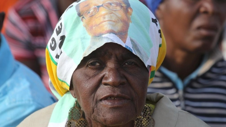 A supporter of Zimbabwean President Robert Mugabe waits for him to arrive at a rally in Bindura about 100 kilometres north east of Harare, Friday, July 8, 2016. Mugabe on Friday blamed sanctions imposed by Western countries for his government's failure to pay salaries on time, in his first public comments after a week of unrest across the county. (AP Photo/Tsvangirayi Mukwazhi)