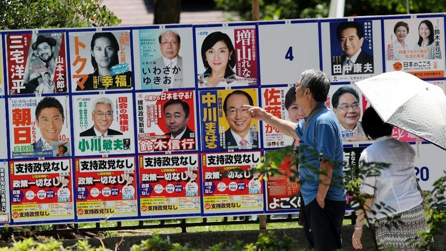 In this July 7, 2016 photo, a man looks at campaign posters with pictures of candidates for the 2016 upper house election in Tokyo.  Japan holds an election Sunday, July 10,  for the upper house of parliament that could affect the country's future direction. While Prime Minister Shinzo Abe's ruling party is seeking a mandate for his leadership by emphasizing his economic revitalization policies, several opposition parties are coordinating a negative campaign, cautioning voters that a landslide for Abe would give him an upper hand to revise the pacifist post-World War II constitution. (AP Photo/Eugene Hoshiko)