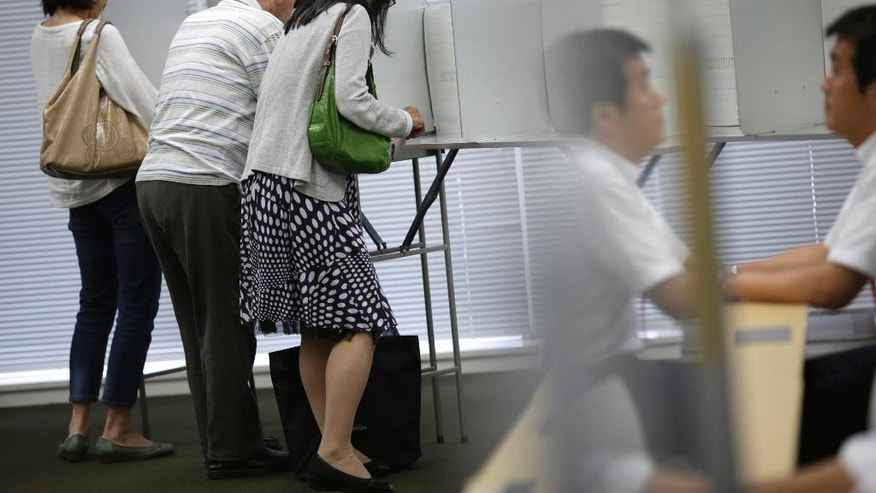 In this July 5, 2016 photo, multiage voters fill the ballot paper at an early voting polling place at Keio University in Yokohama, near Tokyo. Japan holds an election Sunday, July 10,  for the upper house of parliament that could affect the country's future direction. While Prime Minister Shinzo Abe's ruling party is seeking a mandate for his leadership by emphasizing his economic revitalization policies, several opposition parties are coordinating a negative campaign, cautioning voters that a landslide for Abe would give him an upper hand to revise the pacifist post-World War II constitution. (AP Photo/Eugene Hoshiko)
