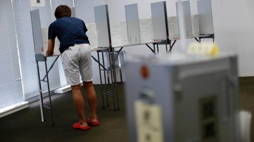 In this July 5, 2016 photo, 18-year-old Fumihiro Yamagishi fills a ballot paper near ballot box at an early voting polling place at Keio University in Yokohama, near Tokyo.  The Sunday, July 10's vote is the first nationwide election since the voting age was lowered to 18 from 20, a step aimed at encouraging voting by younger generations, whose turnout has been extremely low.  (AP Photo/Eugene Hoshiko)