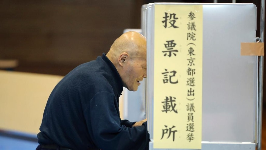 A voters select candidates before casting their ballots in Japan's upper house parliamentary elections at a polling station in Tokyo, Sunday, July 10, 2016.  While Prime Minister Shinzo Abe's ruling party is seeking a mandate for his leadership by emphasizing his economic revitalization policies in the Sunday's election, several opposition parties are coordinating a negative campaign, cautioning voters that a landslide for Abe would give him an upper hand to revise the pacifist post-World War II constitution. (AP Photo/Eugene Hoshiko)