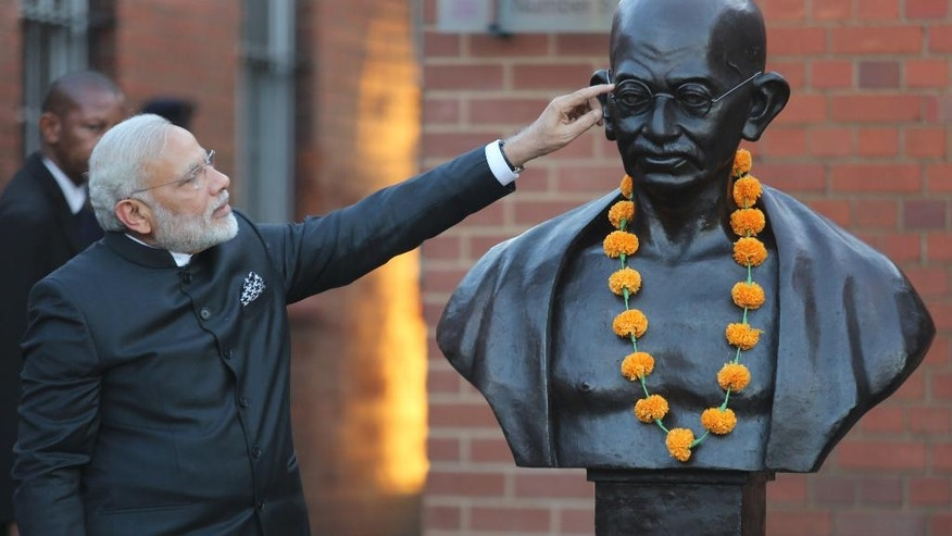 Indian Prime Minister Narendra Modi points at a bust of Mahatma Gandhi on a visit to Constitutional Hill in Johannesburg Friday, July 8, 2016 where he opened the Mandela Gandhi exhibition.  Modi is on the second leg of his trip to Africa as the countries seek closer ties in defense and security. (AP Photo/Denis Farrell)