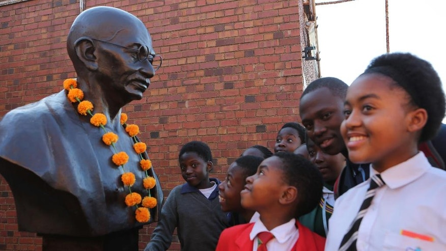 Children look on at a bust of Mahatma Gandhi as they await the arrival of Indian Prime Minister Narendra Modi who visited Constitutional Hill in Johannesburg Friday, July 8, 2016 where he opened the Mandela Gandhi exhibition. Modi is on the second leg of his trip to Africa as the countries sought closer ties in defense and security. (AP Photo/Denis Farrell)