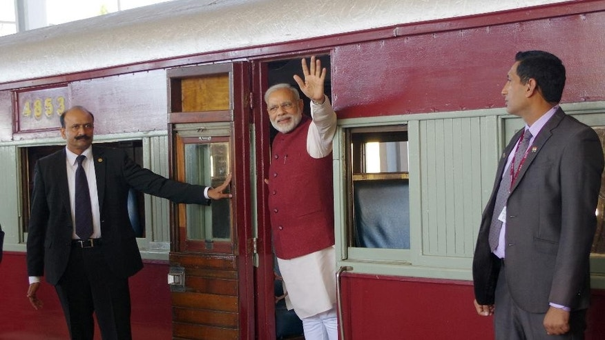 Indian Prime Minister Narendra Modi, waves from a train carriage at Pentrich Railway station in Pietermaritzburg, South Africa, Saturday July 9, 2016.  Narendra Modi is taking the same historic train trip that Mahatma Gandhi took in 1893 when he was thrown off the train because of his race. Modi is on a four nation trip to Africa. (AP Photo)