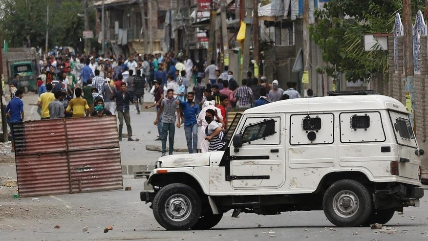 A masked Kashmiri protester throws stones at a police vehicle during a protest in Srinagar, Indian controlled Kashmir, Saturday, July 9, 2016. Indian authorities imposed an indefinite curfew in most parts of Kashmir on Saturday, a day after government forces killed the top rebel commander in the disputed Himalayan region, officials said, describing it as a major success against rebels fighting Indian rule. (AP Photo/Mukhtar Khan)