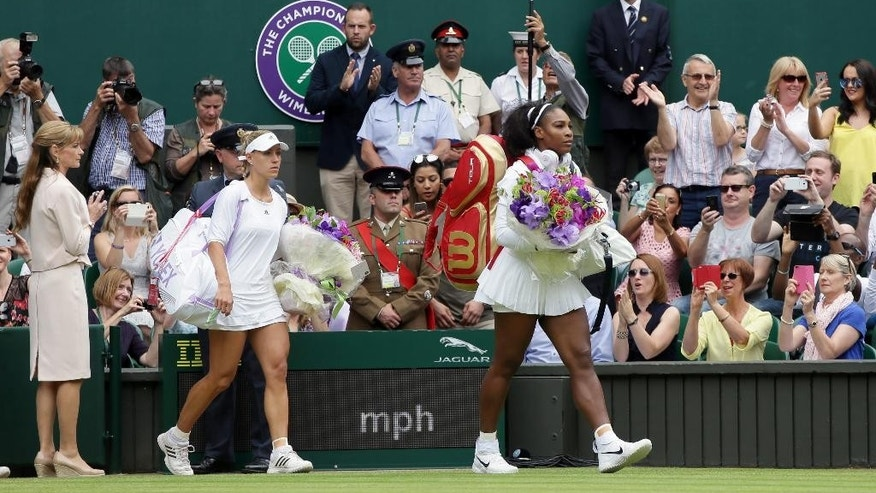 Serena Williams of the U.S, front, and Angelique Kerber of Germany walk on to court for the women's singles final on day thirteen of the Wimbledon Tennis Championships in London, Saturday, July 9, 2016. (AP Photo/Tim Ireland)