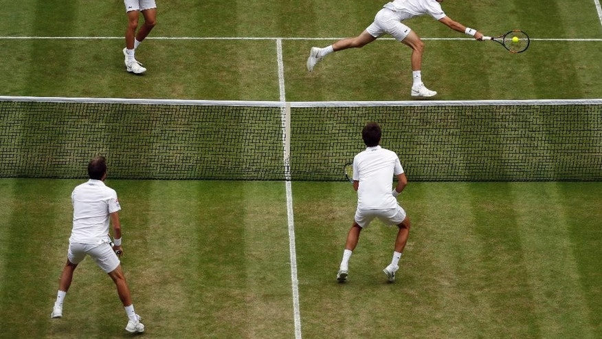 Nicolas Mahut of France, top right, with playing partner Pierre-Hughes Herbert of France return to Julien Benneteau, bottom left, and Edouard Roger-Vasselin of France during the men's doubles final on day thirteen of the Wimbledon Tennis Championships in London, Saturday, July 9, 2016. (AP Photo/Ben Curtis)