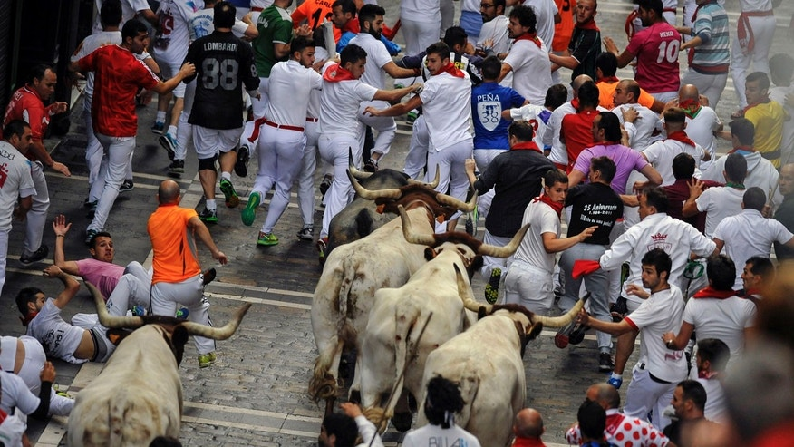 July 9, 2016: Revelers run with Jose Escolar Gil's fighting bulls as they head towards Estafeta street during the third running of the bulls at the San Fermin Festival, in Pamplona, Spain.
