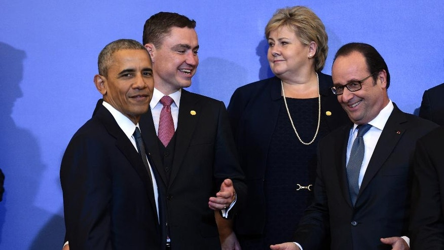 President Barack Obama talks with France's President Francois Hollande, right, as they participates in a NATO family photo at the Presidential Palace in Warsaw, Poland, Friday, July 8, 2016. Obama is in Warsaw to attend the NATO Summit. (AP Photo/Susan Walsh)