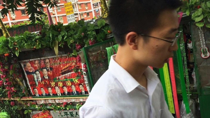 A man walks past a tricycle cart decorated with flowers and a poster with Chinese President Xi Jinping and other top leaders, parked on a street in Beijing, Saturday, July 9, 2016. Overseas bar associations and lawyers groups have issued an open letter to Chinese President Xi Jinping criticizing China's detention of lawyers and activists exactly one year after the crackdown was launched. (AP Photo/Andy Wong)