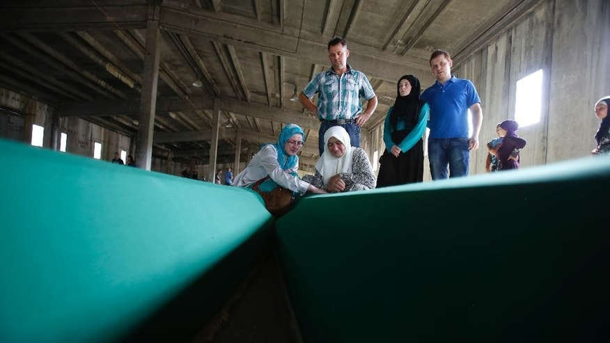 Bosnian Muslim women touch the coffin of a relative among 127 coffins displayed at THE memorial centre of Potocari near Srebrenica, 150 kms north east of Sarajevo, Bosnia, Saturday, July 9, 2016, prior to their burial scheduled for Monday. Thousands of Bosnians raised their hands in prayer Saturday as a truck bearing 127 coffins passed through the capital on its way to Srebrenica, where the newly identified victims of Europe's worst massacre since World War II will be buried on the 21th anniversary of the crime. (AP Photo/Amel Emric)