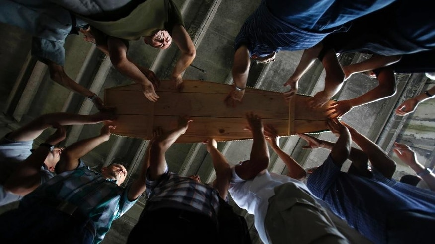 Bosnian Muslim people carry one of 127 coffins with identified victims of the Srebrenica massacre inside a memorial centre of Potocari near Srebrenica, 150 kms north east of Sarajevo, Bosnia, Saturday, July 9, 2016, prior to their burial scheduled for Monday. Thousands of Bosnians raised their hands in prayer Saturday as a truck bearing 127 coffins passed through the capital on its way to Srebrenica, where the newly identified victims of Europe's worst massacre since World War II will be buried on the 21th anniversary of the crime. (AP Photo/Amel Emric)