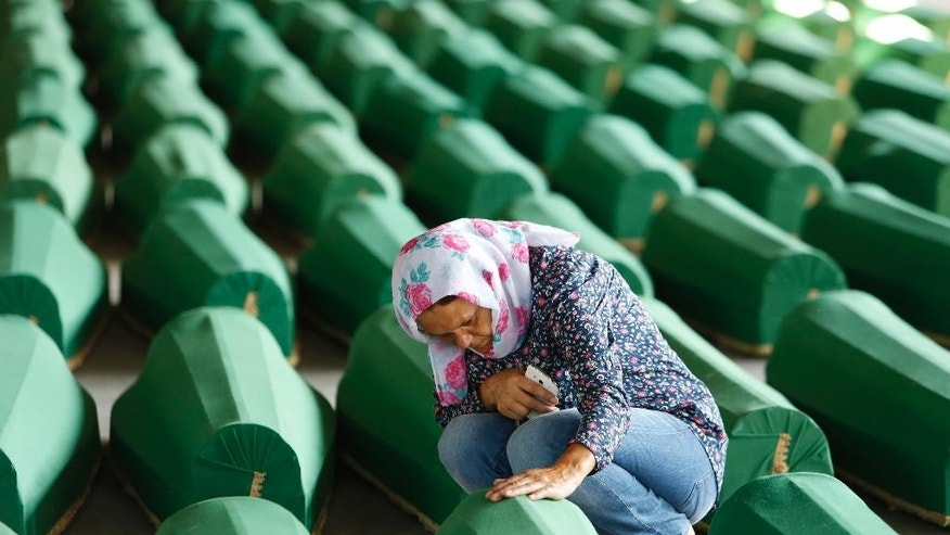 A Bosnian Muslim woman touches the coffin of a relative, among 127 coffins displayed at thememorial centre of Potocari near Srebrenica, 150 kms north east of Sarajevo, Bosnia, Saturday, July 9, 2016, prior to their burial scheduled for Monday. Thousands of Bosnians raised their hands in prayer Saturday as a truck bearing 127 coffins passed through the capital on its way to Srebrenica, where the newly identified victims of Europe's worst massacre since World War II will be buried on the 21th anniversary of the crime. (AP Photo/Amel Emric)