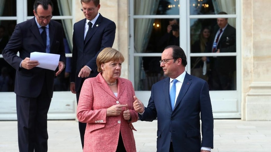 France's President Francois Hollande, right, and German Chancellor Angela Merkel arrive to pose for a family photo during the Balkans summit, at the Elysee Palace, in Paris, Monday, July 4, 2016.The leaders of France, Germany, Italy and Balkan nations are meeting to better prevent extremists from sneaking in with migrants who are moving west across Europe. (AP Photo/Thibault Camus, Pool)