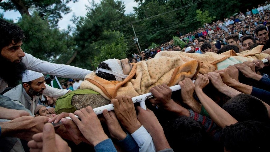 Kashmiri villagers display the body of Burhan Wani, chief of operations of Indian Kashmir's largest rebel group Hizbul Mujahideen, during his funeral procession in Tral, some 38 Kilometers (24 miles) south of Srinagar, Indian controlled Kashmir, Saturday, July 9, 2016. Indian troops fired on protesters in Kashmir as tens of thousands of Kashmiris defied a curfew imposed in most parts of the troubled region Saturday and participated in the funeral of the top rebel commander killed by Indian government forces, officials and locals said. (AP Photo/Dar Yasin)