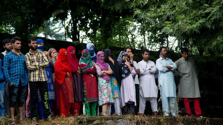 Kashmiri villagers watch the funeral procession of Burhan Wani, chief of operations of Indian Kashmir's largest rebel group Hizbul Mujahideen, in Tral, some 38 Kilometers (24 miles) south of Srinagar, Indian controlled Kashmir, Saturday, July 9, 2016. Indian troops fired on protesters in Kashmir as tens of thousands of Kashmiris defied a curfew imposed in most parts of the troubled region Saturday and participated in the funeral of the top rebel commander killed by Indian government forces, officials and locals said. (AP Photo/Dar Yasin)