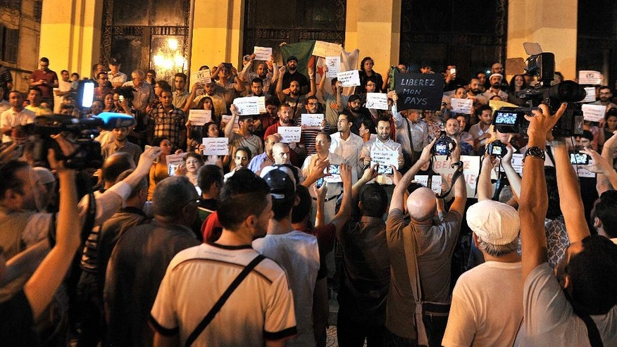 "In this  Friday, July 1, 2016  photo, Algerian journalists and other intellectuals stage a protest against government crackdown in front of the national theater in Algiers, Algeria. Algerian officials are going after the independent media for unnecessarily ""setting off alarms"" and ""darkening"" the image of the North African country, which is struggling with lost oil revenues and political uncertainty surrounding an ailing president. (AP Photo/Anis Belghoul)"