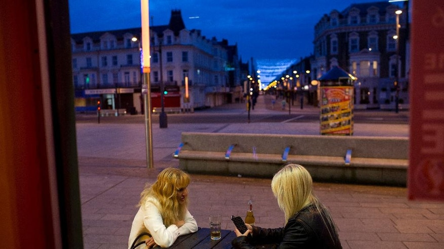 In this Wednesday, July 6, 2016 photo, two woman sit outside a pub at Great Yarmouth, East of England. Not just in this quintessentially English, declining seaside resort but throughout the United Kingdom, people who voted to leave the European Union say the sense of community that once glued the country together had been shattered. They blamed politicians, bankers, foreigners, European bureaucrats and even political correctness. (AP Photo/Emilio Morenatti)