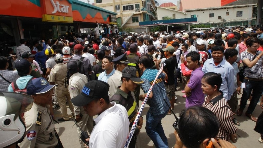 People stand outside a shopping mall where Kem Ley, a prominent political analyst, was shot and killed, in Phnom Penh, Cambodia, Sunday, July 10, 2016.  Police in Cambodia say a dispute over money led to the shooting death of Kem Ly at a shopping mall in the capital Phnom Penh.  (AP Photo/Heng Sinith)