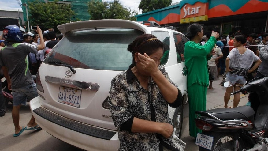 A Cambodian woman, foreground, weeps outside a local market where Kem Ley, a political analyst, was killed in Phnom Penh, Cambodia, July 10, 2016. Police in Cambodia say a dispute over money led to the shooting death of a prominent political analyst at the shopping mall in the capital Phnom Penh. (AP Photo/Heng Sinith)