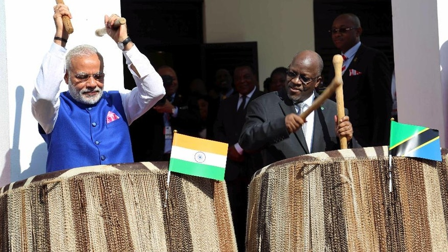 Indian Prime Minister Narendra Modi, left, and his host Tanzanian President John Pombe Magufuli, right, beat drums at the entrance of State House during an official welcome ceremony for Modi in Dar es Salaam Tanzania Sunday July 10, 2016. Modi is on his third leg of his Africa tour. (AP Photo/Khalfan Said)