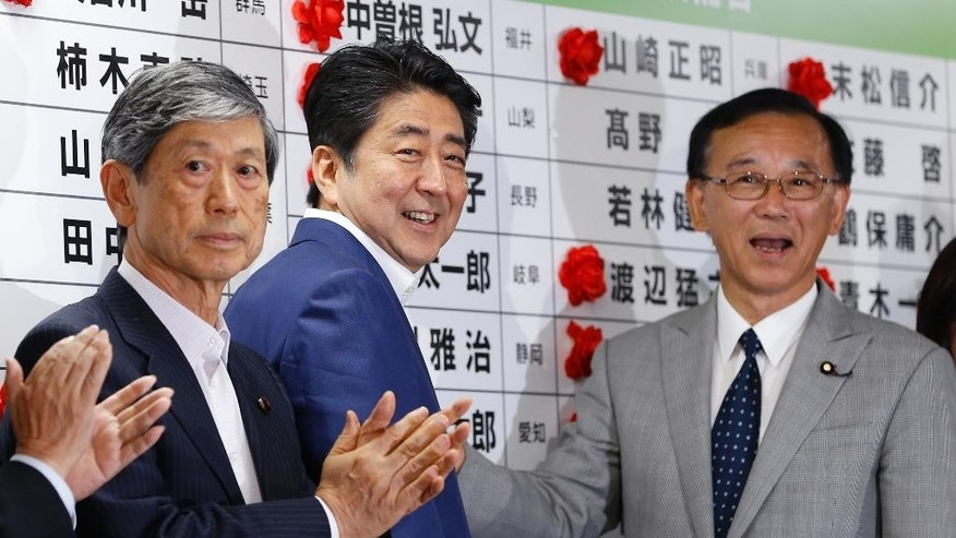 Japan's Prime Minister Shinzo Abe, center, and leader of the Liberal Democratic Party, smiles as he places a red rosette on the name of his Liberal Democratic Party's winning candidate during ballot counting for the parliamentary upper house elections at the party headquarters in Tokyo, Sunday, July 10, 2016. (AP Photo/Shizuo Kambayashi)