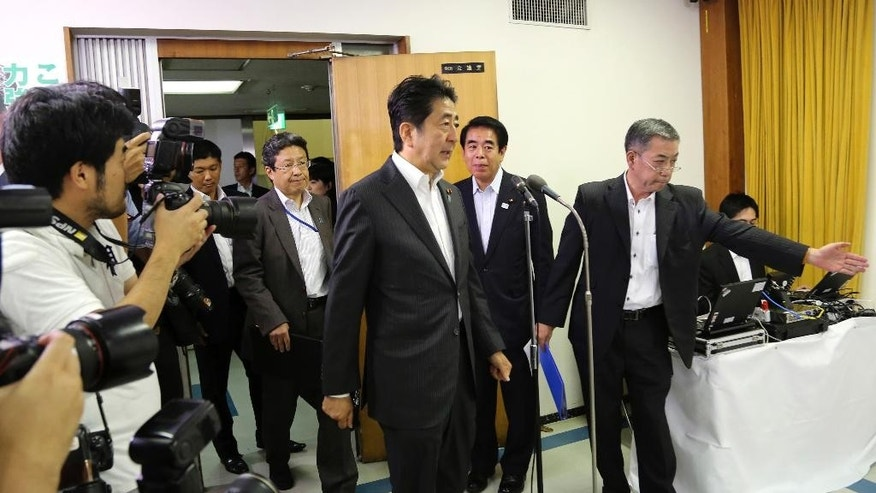 Japanese Prime Minister and leader of the ruling Liberal Democratic Party, Shinzo Abe, center, arrives for a press conference at the party headquarters in Tokyo, Monday, July 11, 2016. A resounding election victory for Abe's ruling bloc has opened the door a crack for his long-cherished ambition to revise the constitution for the first time since it was enacted in 1947 - a behind-the-scenes agenda that could over time change Japan's future. (AP Photo/Koji Sasahara)