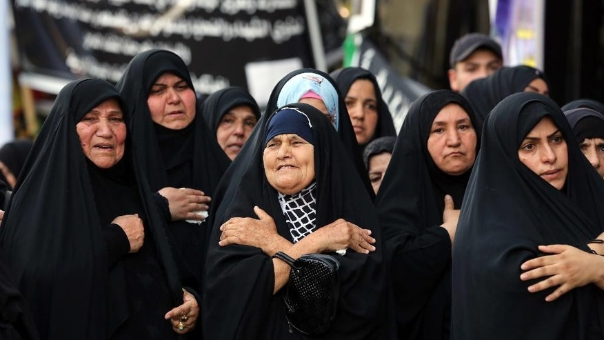 People grieve during a symbolic funeral for the victims of a massive truck bombing last Sunday that killed at least 186 people and was claimed by the Islamic State group, in the Karada neighborhood of Baghdad, Iraq, Sunday, July 10, 2016. (AP Photo/Hadi Mizban)