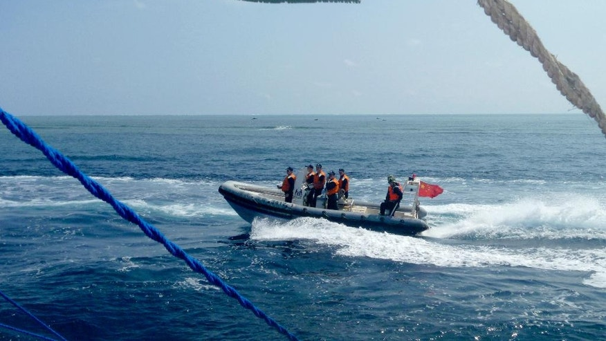 FILE - In this Oct. 27, 2015, file photo, provided by Filipino fisherman Renato Etac, a Chinese Coast Guard boat circles a Filipino fishing boat near Scarborough Shoal in the South China Sea. China has intensified the drumbeat of its opposition to a milestone ruling expected Tuesday July 12, 2016, by an international tribunal that could threaten its expansive claims in the South China Sea. (Renato Etac via AP, File )