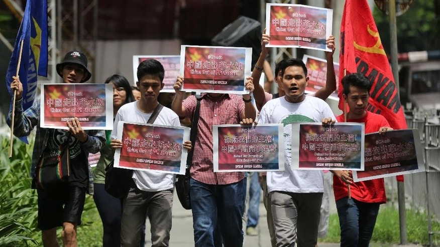 Filipino activists hold slogans as they walk towards the Chinese consulate to protest China's territorial claim over the disputed Spratlys island group during a rally at the financial district of Makati, south of Manila, Philippines on Monday, July 11, 2016.   A landmark ruling on an arbitration case filed by the Philippines that seeks to strike down China's expansive territorial claims in the South China Sea will be a test for international law and world powers. China, which demands one-on-one talks to resolve the disputes, has boycotted the case and vowed to ignore the verdict, which will be handed down Tuesday by a tribunal in The Hague. (AP Photo/Aaron Favila)