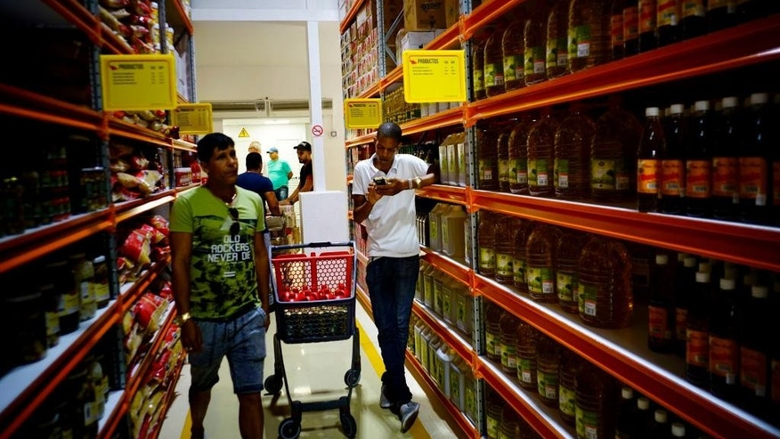 Shoppers walk through the aisles of a new bulk goods store in Havana, Cuba, Monday, July 11, 2016. Called Zona +, the high-ceiling space has racks stacked with large tins of tomato sauce, toilet paper and cooking oil by the gallon. (AP Photo/Ramon Espinosa)